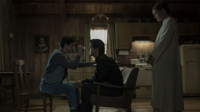 Hamish Linklater as Father Paul gets his vision checked out by the town doctor while the villainous Ben Keane watches as seen in MIDNIGHT MASS directed by Mike Flanagan on Netflix.