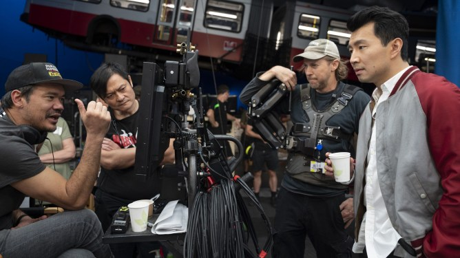 Director Destin Daniel Cretton directs an action set piece on a train with lead star Simu Liu on the set of SHANG-CHI AND THE LEGEND OF THE TEN RINGS.