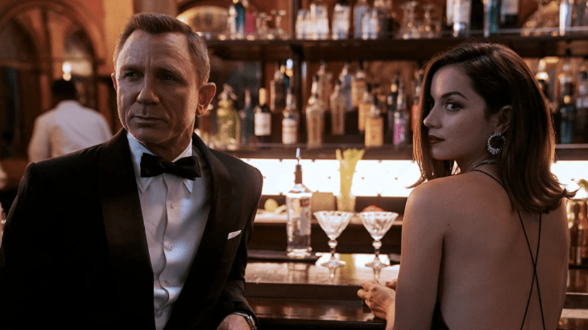 Daniel Craig as James Bond with Ana de Armas in a backless dress sit together at a Cuban bar in NO TIME TO DIE directed by Cary Fukunaga.