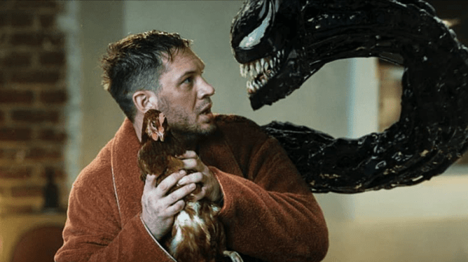 Tom Hardy holds a chicken while wearing a night robe as he's confronted by the Venom Symbiote coming out of his body in VENOM: LET THERE BE CARNAGE.
