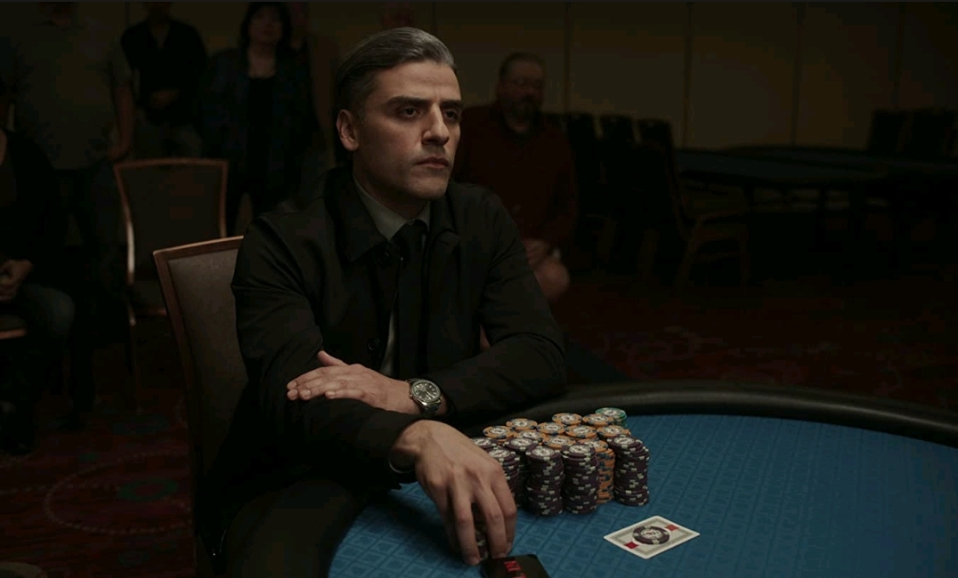 Oscar Isaac playing competitive poker with a straight blank face as seen in THE CARD COUNTER directed by Paul Schrader.