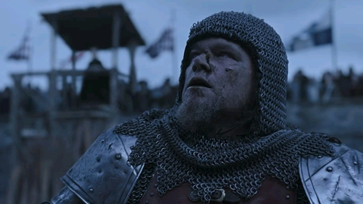 Matt Damon as Jean de Carrouges bloodied and looking defeated in knight's armor as seen in THE LAST DUEL directed by Ridley Scott.