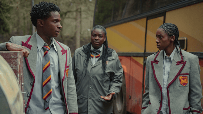 Jackson, Viv, and Cal stand together in front of a school bus all wearing the new Moordale school uniforms as seen in SEX EDUCATION season 3 on Netflix.