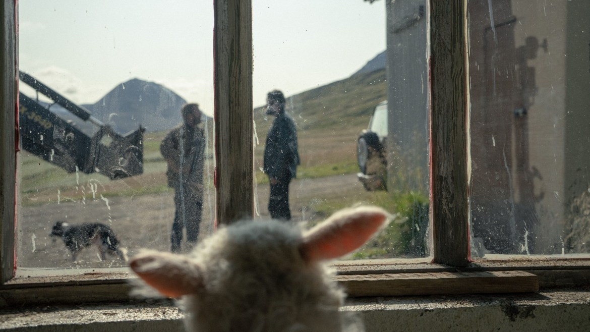 Ada the small half-human, half-sheep hybrid stares at her adopted father and uncle from inside a barn window as seen in the new A24 film LAMB.
