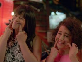 Broad City's Abbi and Ilana hold up smiles with their middle fingers. It's irony!