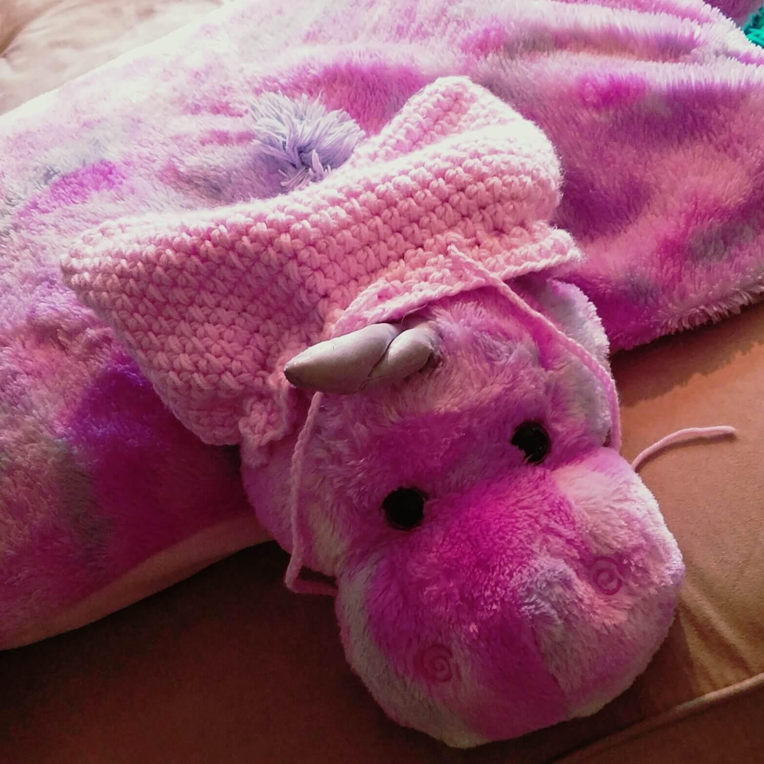 pink stuffed unicorn wearing one of the women's march pink hats