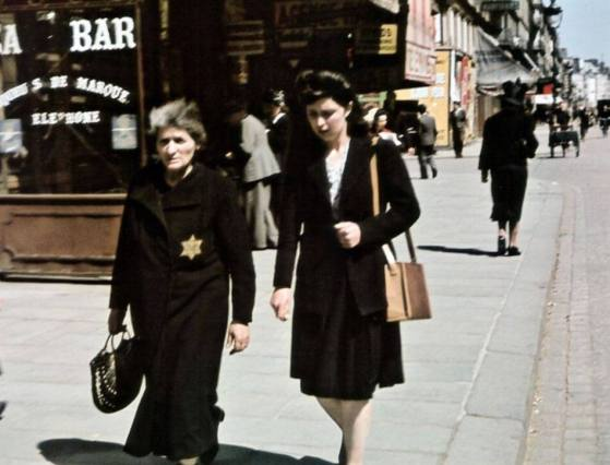 Two women on a Paris street. One wears a yellow star of David
