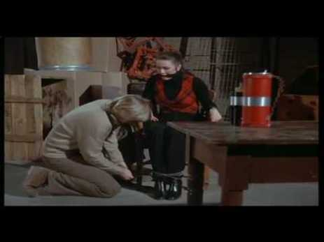 A white woman being tied to a chair by a blonde man