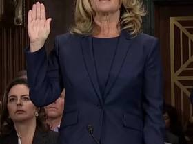 Christine Blasey Ford Woman with blonde hair and glasses with her hand raised