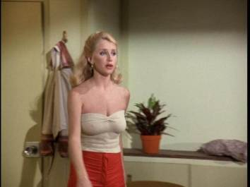 Suzanne Somers wearing a tan tube top and red pants