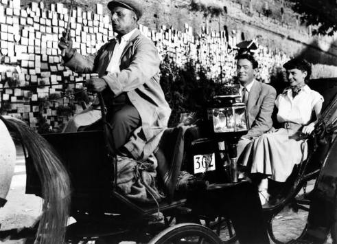 Audrey Hepburn and Gregory Peck in a horse drawn carriage in Roman Holiday