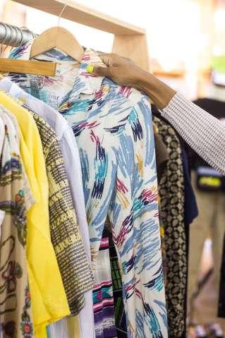 ladypreneur Lesly Washington's shop tchoup vintage. A woman's hand pulling colorful dress off a rack