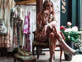 Woman sitting on armchair surrounded by clothes and flowers. Fashion YouTubers
