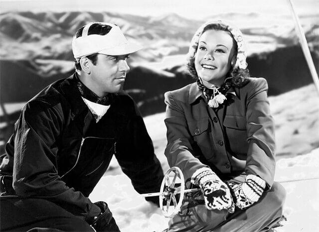 Sonja Henie and John Payne sitting in snow wearing winter film fashions