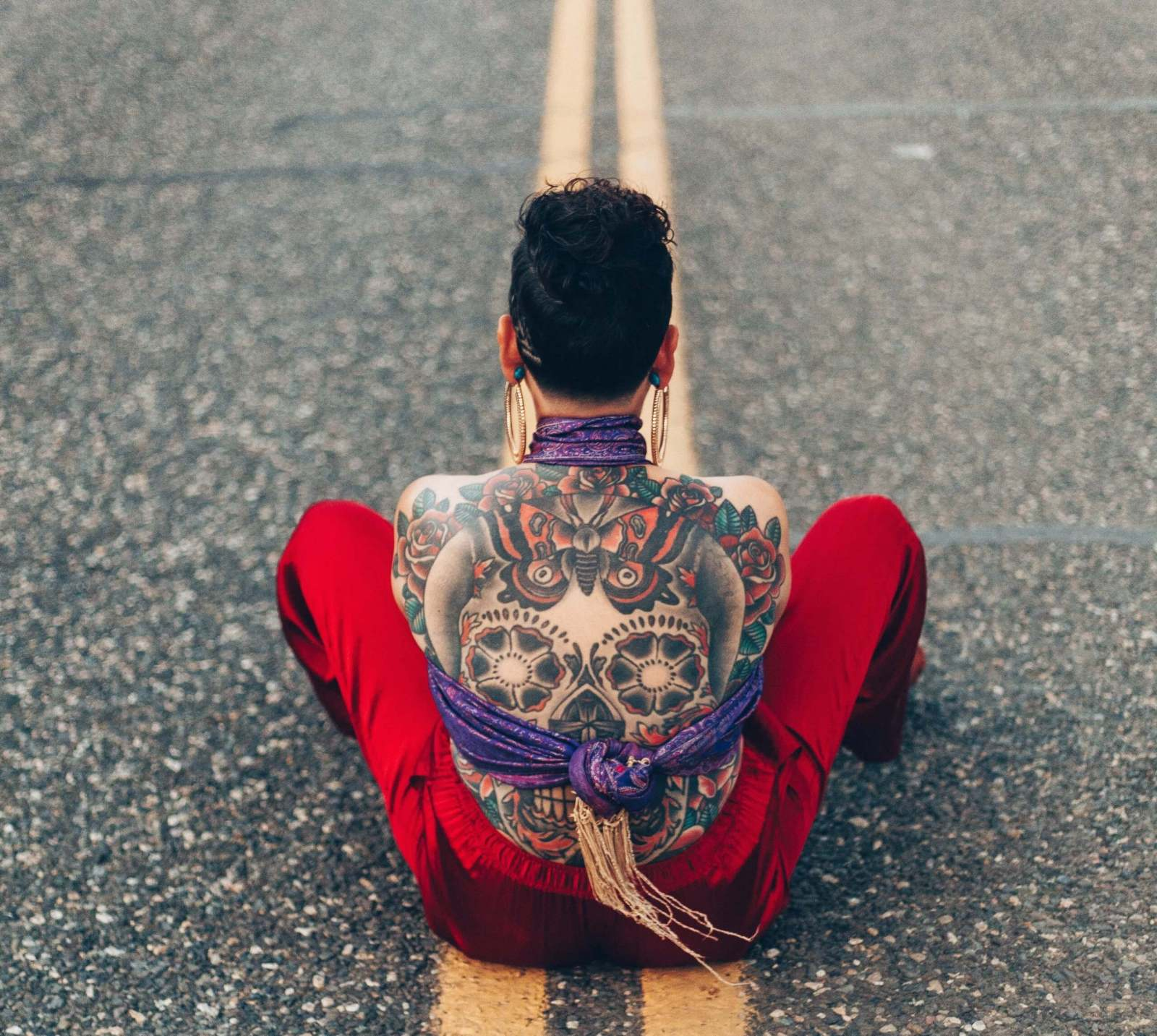 Woman sitting on a road. Her back has elaborate tattoo