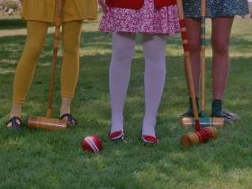 Gen X Heathers legs in colorful tights and croquet mallets