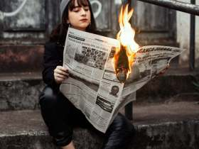 A young white woman with a flaming newspaper that could be ourFall 2020 Newsletter