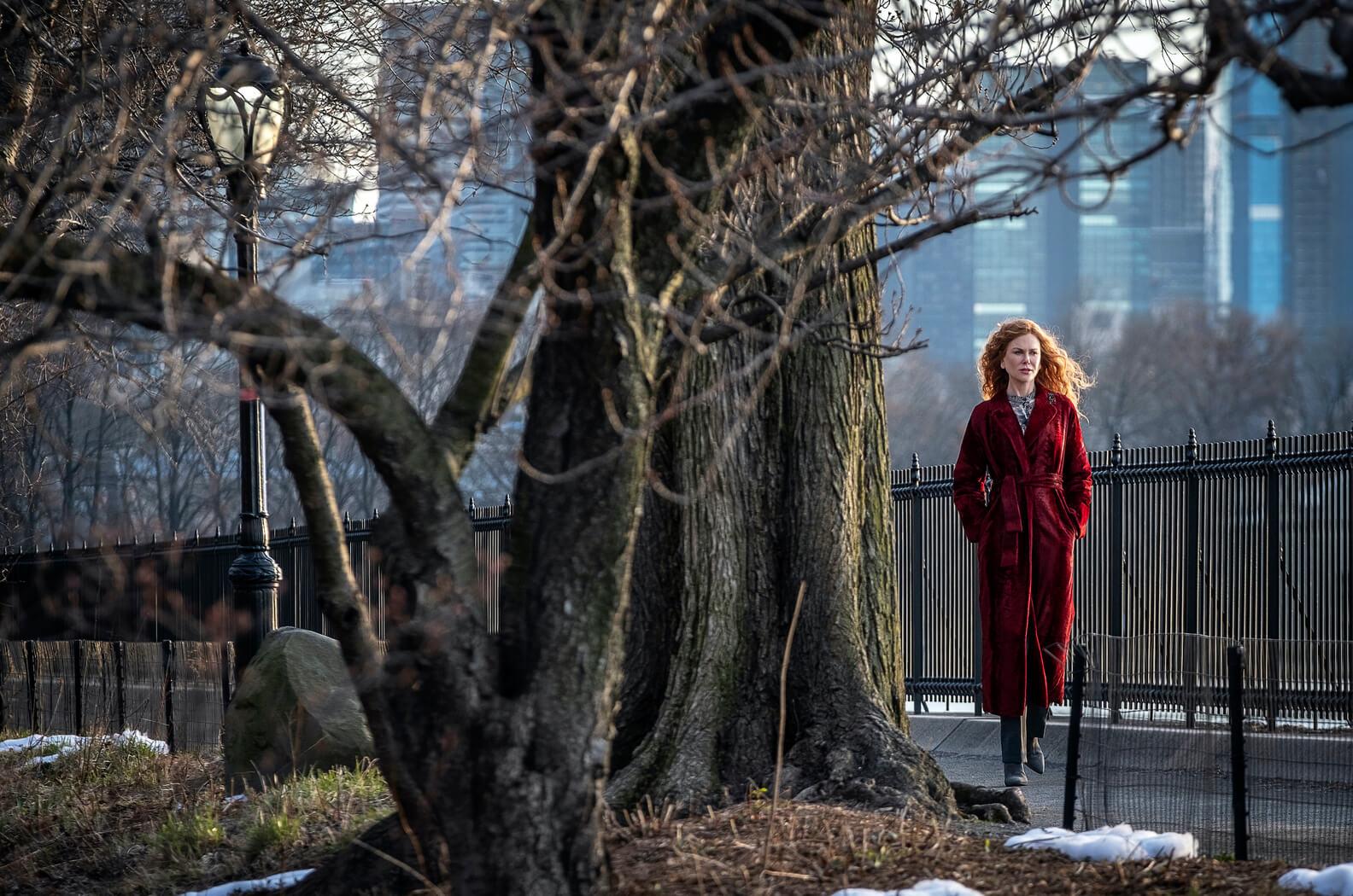Nicole Kidman walking alone in long red coat