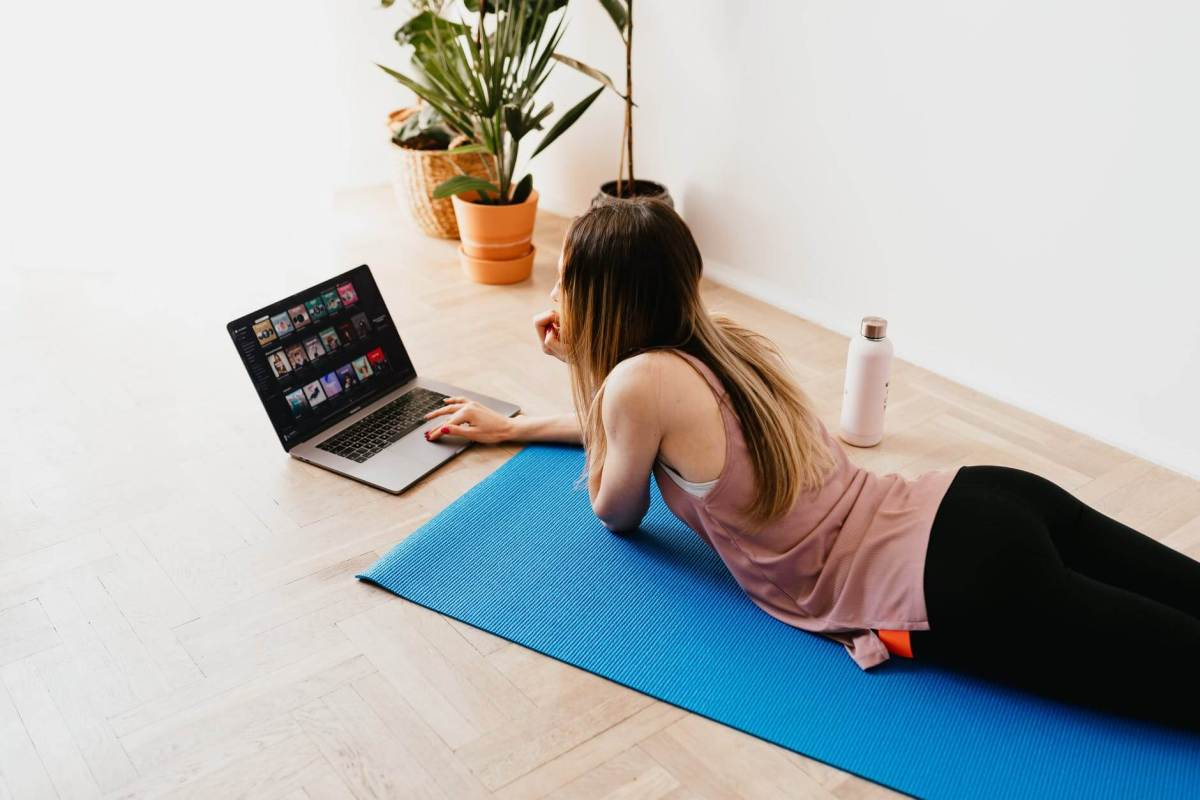 online yoga young woman lying on floor on mat while using laptop at home