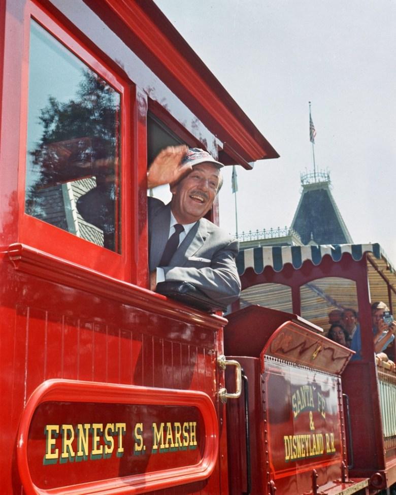 Walt Disney saludando desde un carro de tren rojo