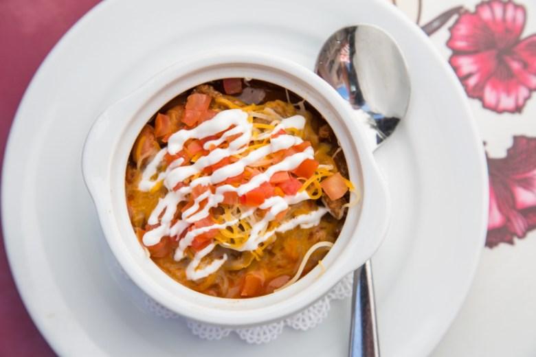 Un tazón de chili beans con crema y queso sobre un plato blanco y una cuchara a un lado