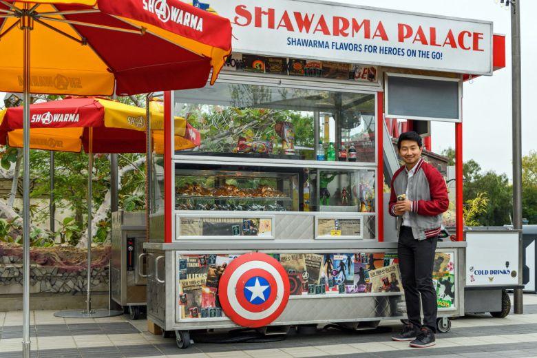 Simu Liu enfrente de Shawarma Palace en Avengers Campus