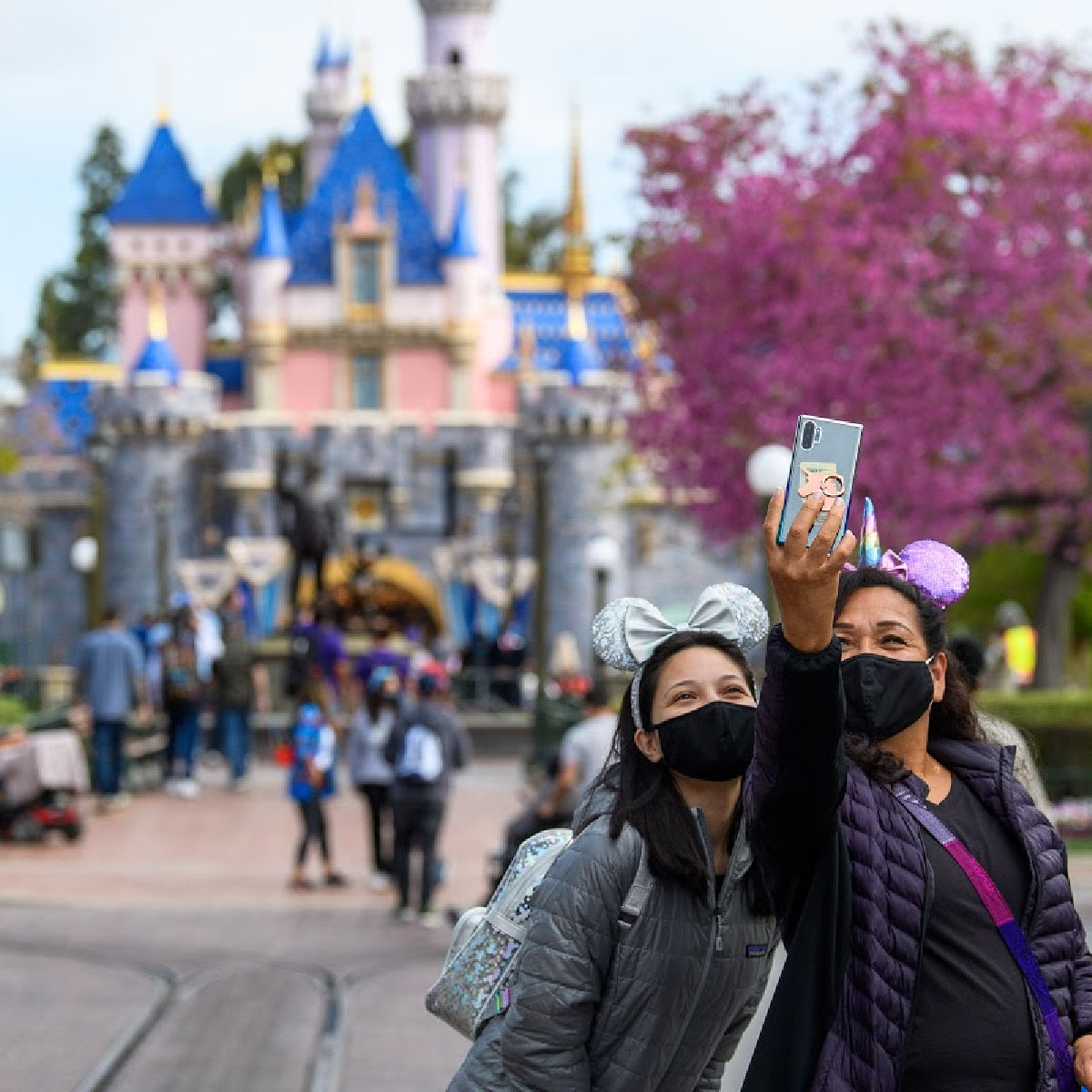 dos chicas con tapabocas tomándose foto enfrente del castillo durante la reapertura de Disneylandia