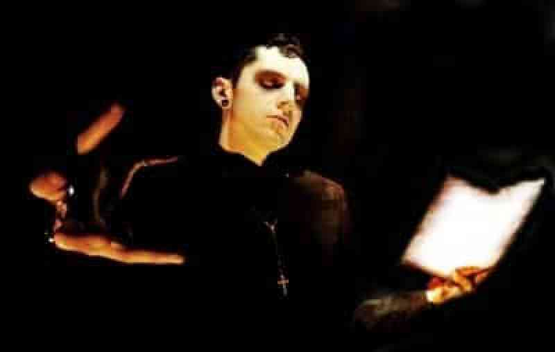 the frontman of Distorted Memory dressed like a goth vicar reading a psalm