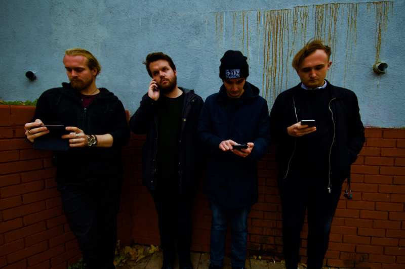 Sugar Horse press shot of them all on their phones