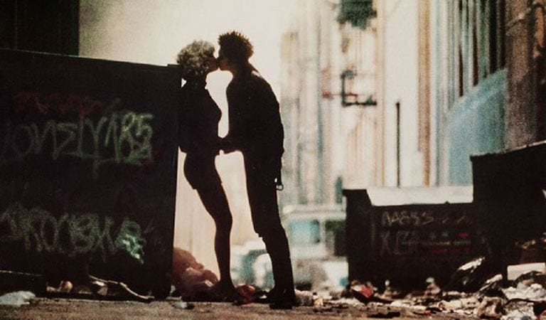 sid and nancy kiss next to a trash can