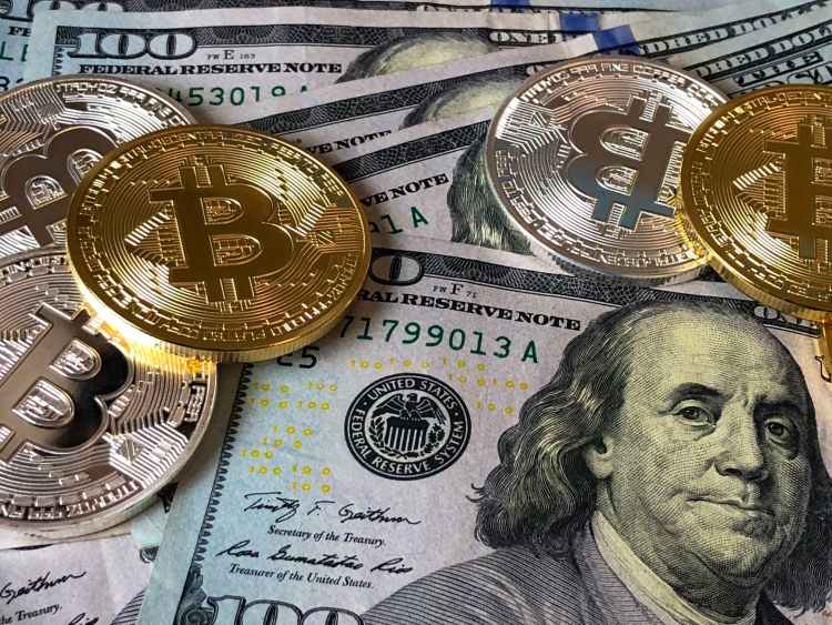 image of cold coins with the letter B inscribed representing bitcoins laying on top of 100 dollar bills displaying ben franklin