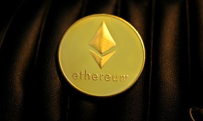 gold round coin with ethereum logo on black textile