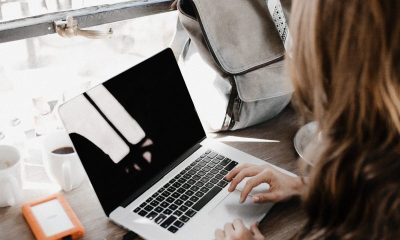 girl wearing grey long-sleeved shirt using MacBook Pro on brown wooden table
