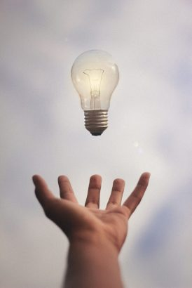 Light bulb floats in the air above a hand.