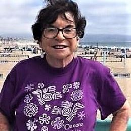 Joan has short black hair, dark rimmed glass, and stands in front of a beach looking into the camera. She wears a purple shirt with white designs.