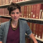 Picture of Cassandra standing in front of a book shelf. She has short hair, and is looking at the camera. She is wearing a grey blazer with a purple top.