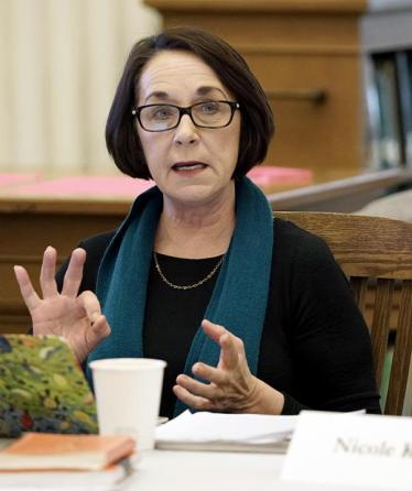 Dr Brenda Bruggerman is shown gesturing with her hands while talking at a conference. She is wearing a black shirt and necklace, with a simple teal scarf. She is light skinned and has black hair worn in a bob, and glasses with rectangular frames.