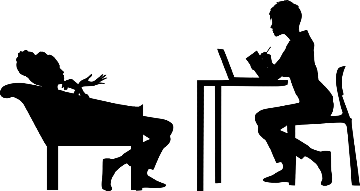 a person slouched in a chair in front of another person at a desk who is paying attention to what they are saying