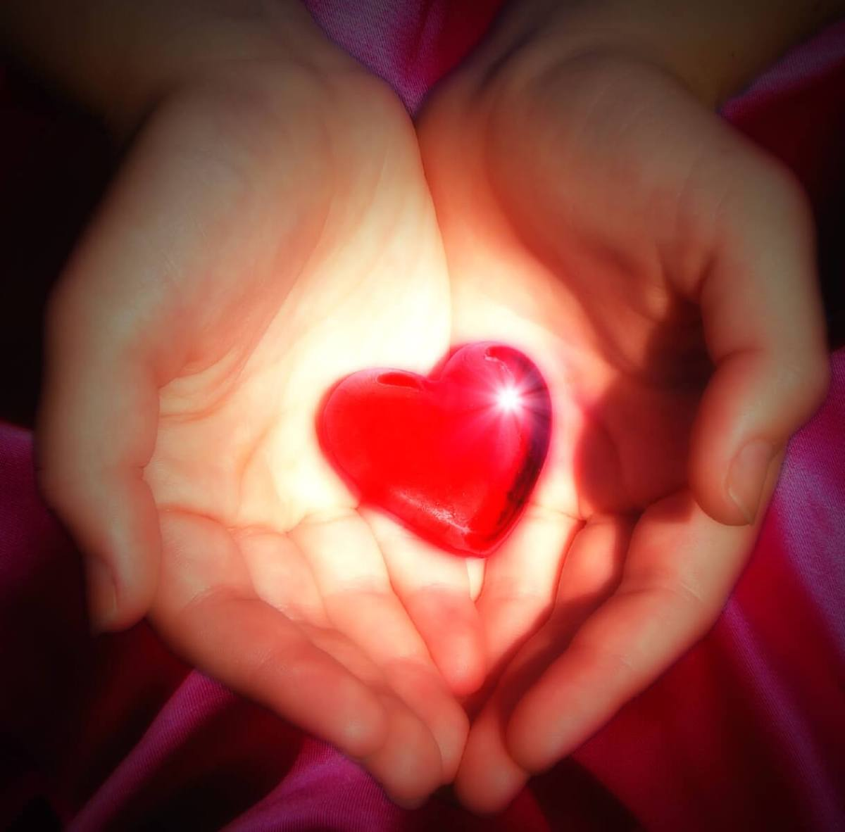 two cupped hands holding a glowing heart