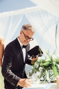 Celebrant Ulf is wearing a formal dark suit and bow tie as he officiates at a wedding in Mallorca. Here he is signing the wedding certificate.