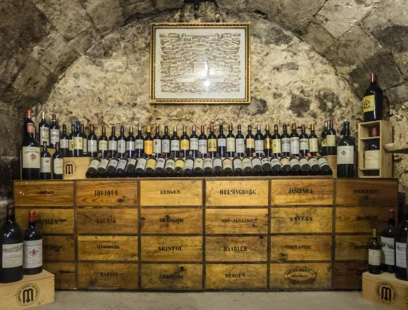 Cellar Worthy Wine A round roofed wine cellar with bottles displayed on top of drawers filled with wine.