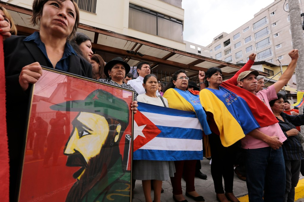 People gather with Cuban and Ecuadorean national flags outside the Cuban embassy in Quito on November 26, 2016, the day after Cuban historic revolutioonary leader Fidel Castro died aged 90. Cuban revolutionary icon Fidel Castro died late Friday in Havana, his brother, President Raul Castro, announced on national television. Castro's ashes will be buried in the historic southeastern city of Santiago on December 4 after a four-day procession through the country. / AFP PHOTO / JUAN CEVALLOS