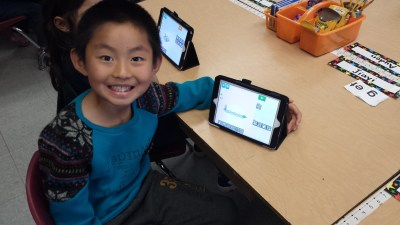 First graders completing the Hour of Code Lightbot tutorial on iPads.