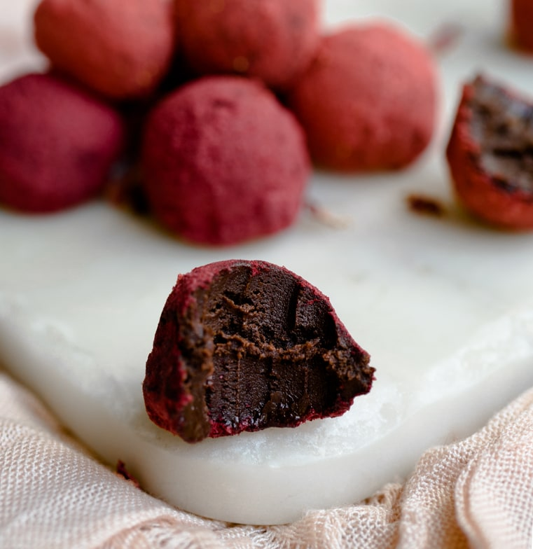 Chocolate red wine truffles rolled in berry dust and stacked on top of each other. Close up on one that's been bitten from showing texture and teethmarks.