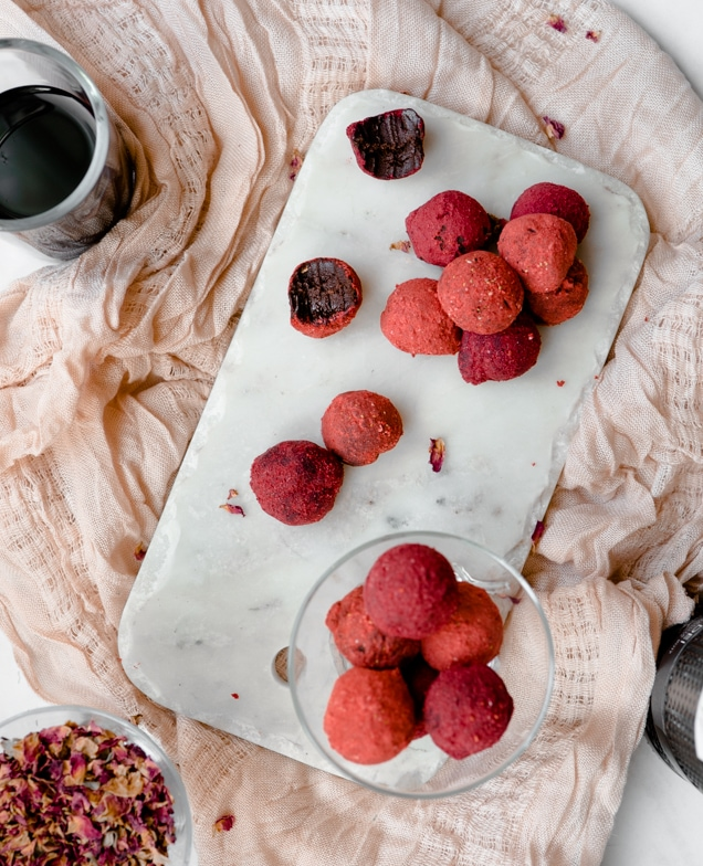 Red wine chocolate truffles rolled in berry dust sitting on a marble platter with a couple bitten from. Next to wine and dried rose petals on a pink linen.