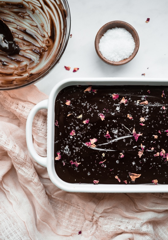 Melted truffle mixture in a small dish topped with flaky sea salt and dried rose petals next to empty bowl of chocolate.