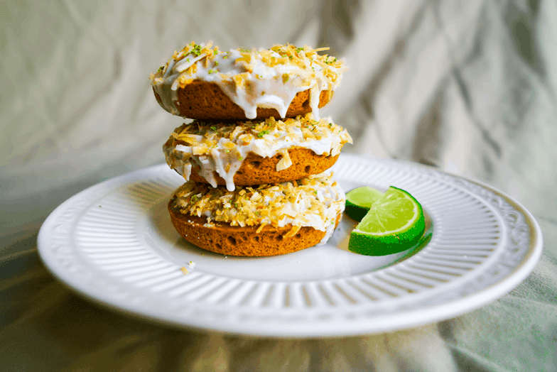 Three coconut lime donuts stacked on top of each other on a saucer with two lime wedges.