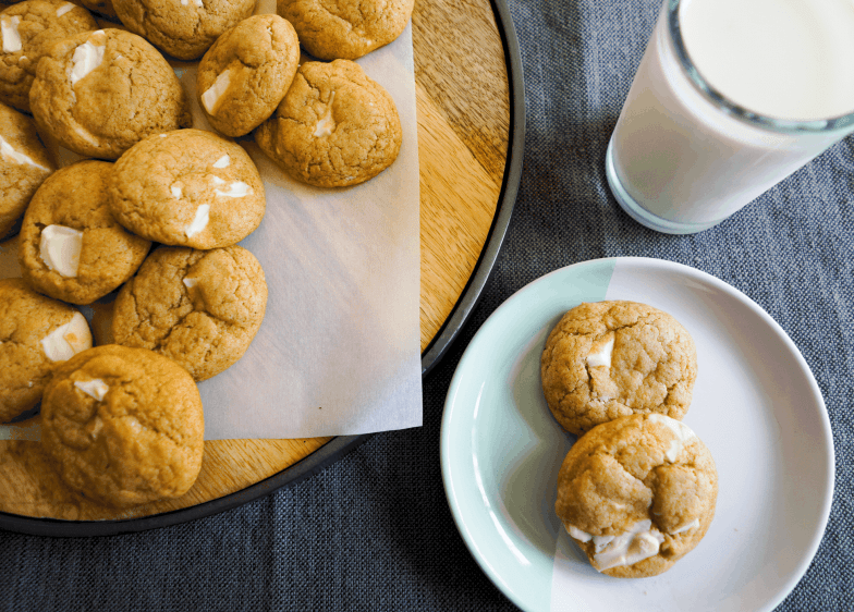 Platter of chewy pumpkin brown butter white chocolate chunk cookies with a glass of milk.