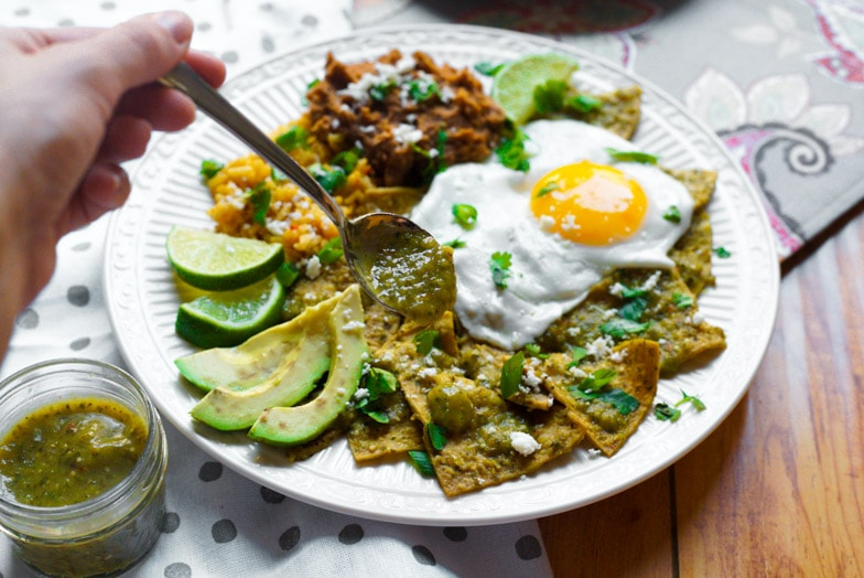 Plate of air fryer chilaquiles verdes with a sunny side up egg being topped with extra tomatillo salsa.