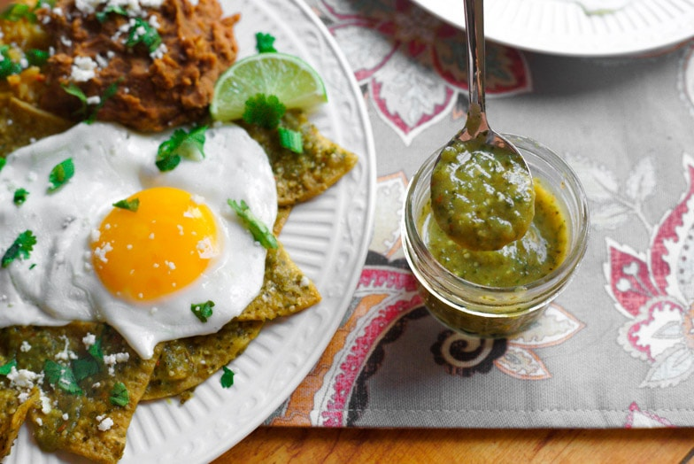 Spoon dipping into a jar of tomatillo salsa next to a plate of air fryer chilaquiles verdes with a sunny side up egg.